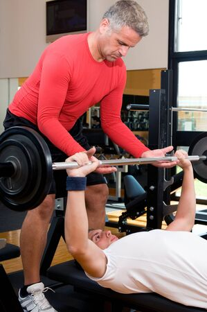 Young man doing weigths on a bench press with the help of the mature instructor at gym Stock Photo - 7889502