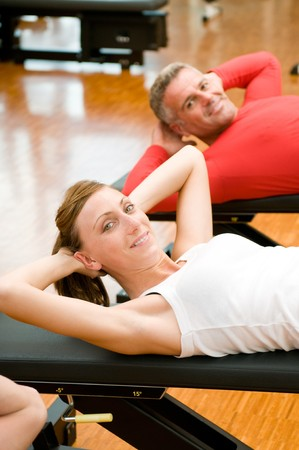 Young lady making sit-ups on bench at gym photo