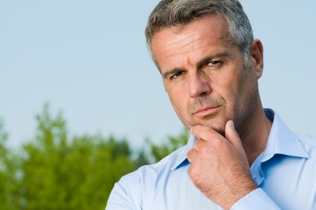 Modern pensive mature businessman looking at camera photo