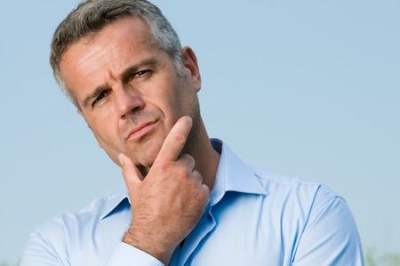 confus: Homme mature perplexe regardant cam�ra en plein air Banque d'images