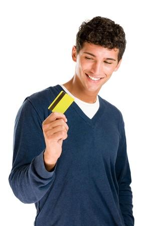 tarjeta de credito: Feliz y sonriente hombre joven mirando su tarjeta de cr�dito aislado sobre fondo blanco
