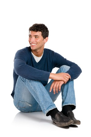 sitting floor: Smiling young man looking away with embarassement isolated on white background