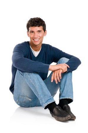 sitting on floor: Happy smiling young man sitting on floor isolated on white background