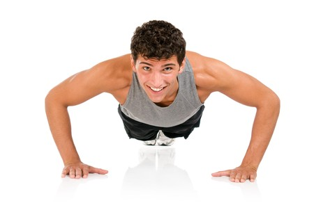 Young smiling fitness man doing push ups on floor, studio shot isolated on white background Stock Photo - 7889362