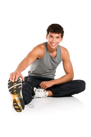 Happy smiling young fitness man sitting and making stretching exercises after gym isolated on white background photo