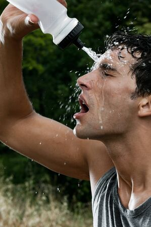 Young tired athlete splashing and pouring fresh water on his head to refresh during a running trail photo