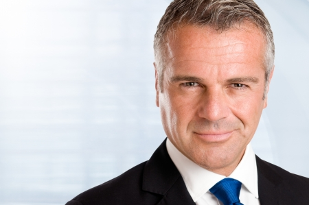 mature male: Closeup portrait of satisfied mature businessman in his office with copy space