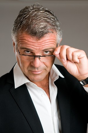 Mature man holding and putting on a pair of glasses with satisfaction photo