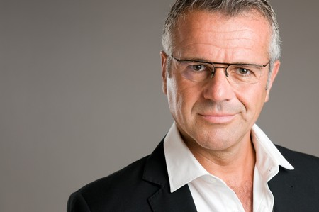 Mature man with pair of glasses looking at camera with satisfaction photo