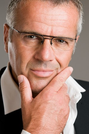 Confident pensive mature man with glasses looking at camera satisfied photo