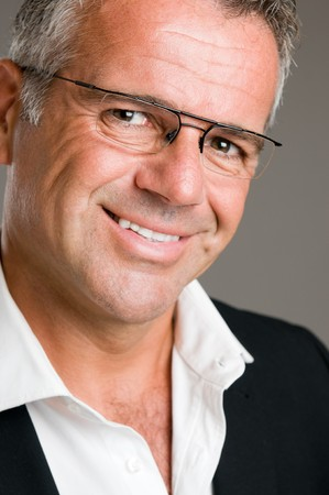Smiling mature man looking at camera with a pair of glasses  photo