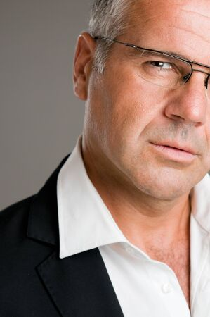 Closeup portrait of pensive mature man with glasses photo