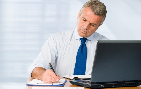 Absorbed mature businessman working and taking notes in his modern office photo