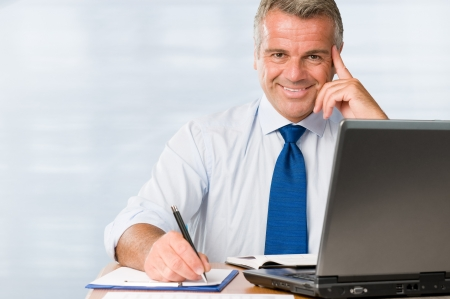 satisfied: Satisfied mature businessman smiling in his modern office at work