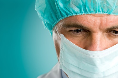 Closeup portrait of a mature male surgeon in the operating room, space for text photo