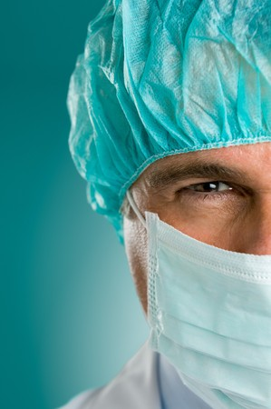 Mature male surgeon gazing and looking at camera at hospital