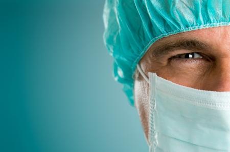 Oudere mannelijke chirurg staren en kijken naar camera in zieken huis, close-up shot Stockfoto