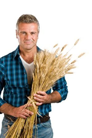granjero: Feliz y satisfecho agricultor maduro sosteniendo un manojo de trigo despu�s de la cosecha aislada sobre fondo blanco