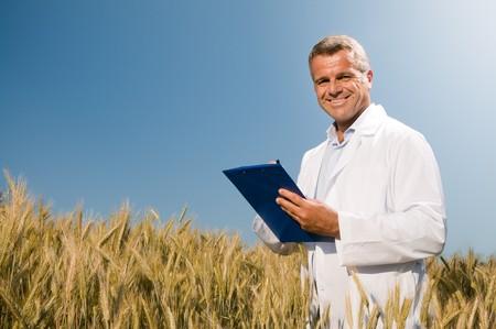 control de calidad: Feliz t�cnico maduro comprobando el crecimiento del trigo para un control de calidad en un campo de cereales en verano  Foto de archivo