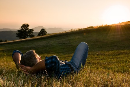 break in: Mature man taking a break and relax in a meadow in the wonderful warm light of the sunset