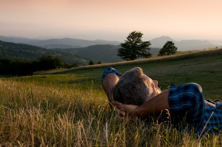 positive positivity: Closeup view of mature man taking a break and relax in a meadow in the wonderful warm light of the sunset Stock Photo