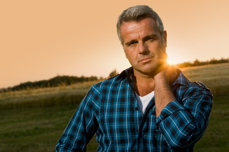 Mature man relax and looking at camera with satisfaction in the wonderful light of the sunset Stock Photo - 7889434
