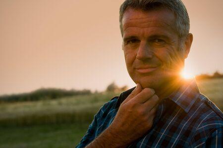 農家: 中年の男の休憩を取って、夕日の素晴らしい暖かい光の草原でリラックス