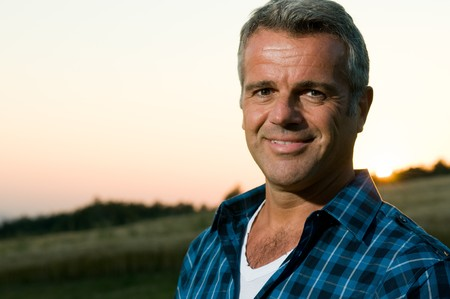 smiling sun: Happy smiling mature man looking at camera outdoor in a meadow