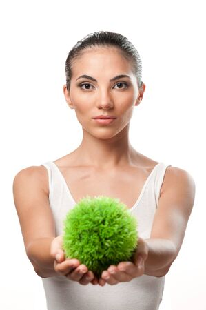 Beautiful young woman holding a sphere of green grass, symbol of care and protection of the natural environment Stock Photo - 7889404
