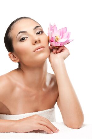 Beautiful young woman with lotus flower lying on white towel during a spa treatment over white background, professional beauty makeup Stock Photo - 7889402