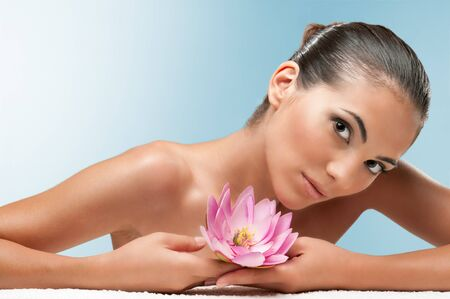 Beautiful young woman lying on white towel during a spa treatment over a light blue background, professional beauty makeup photo