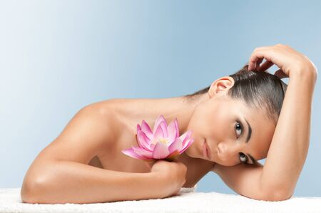 Beautiful young woman with lotus flower lying on white towel during a spa treatment over a light blue background, professional beauty makeup Stock Photo - 7889418