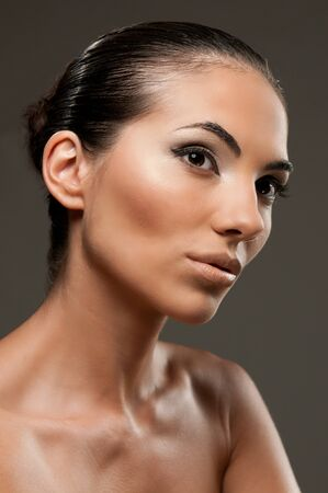 Fashion and beauty model portrait over gray background, perfect professional makeup photo