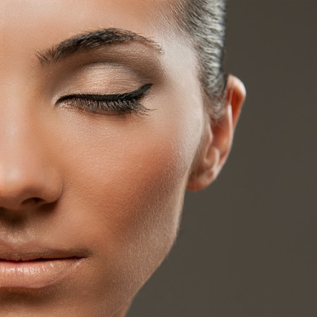 Closeup shot of half beautiful female model face with professional fashion makeup photo