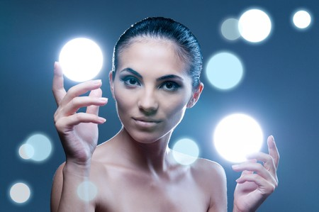 Beautiful fairy female model holding sphere of light on her hands, professional beauty makeup photo