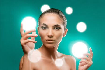 Beautiful fairy female model holding spheres of light on her hands, professional beauty makeup photo