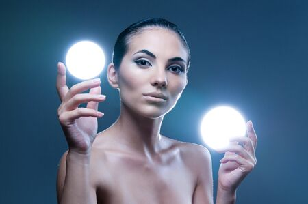 Beautiful fairy female model holding two spheres of light on her hands, professional beauty makeup photo