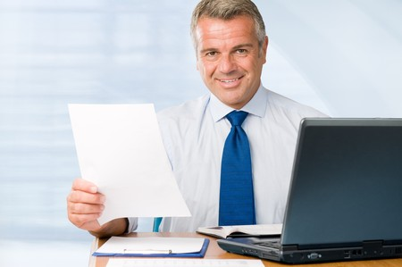 Mature positive businessman holding paperwork and looking at camera smiling photo