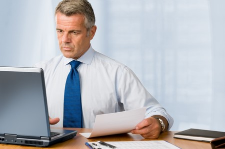 Mature businessman looking and analyzing document in his modern office at work Stock Photo - 7889587