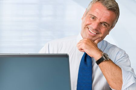 businessman with laptop: Successful mature businessman looking at camera behind his laptop at work in office