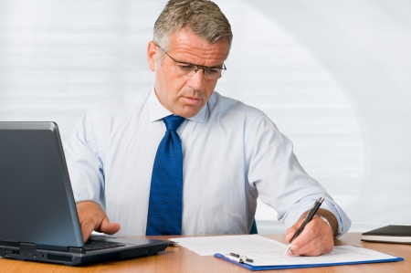 Mature businessman writing on paperwork and working with laptop in his office photo