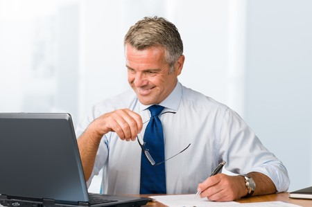 Happy smiling businessman working with paperwork and laptop in his modern office Stock Photo - 7889586