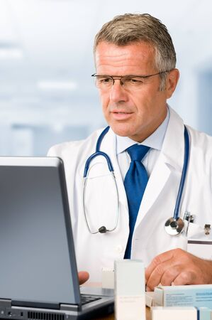Mature doctor working on laptop and making medications prescriptions in his clinic office photo