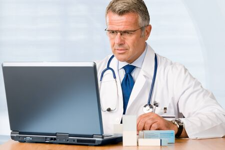 Mature doctor working on laptop and medications cases to make prescriptions in his clinic office photo