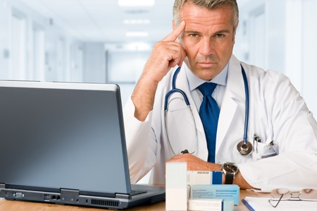doctor computer: Serious mature doctor looking and gazing at you while working with  laptop and medications cases to make prescriptions in his clinic office