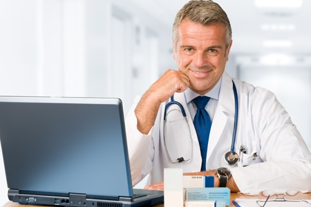 doctor laptop: Happy satisfied mature doctor working and looking at camera in his modern clinic office Stock Photo
