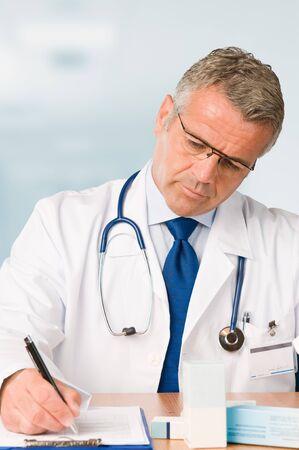 recetas medicas: Maduro m�dico escrito y prescribir un examen m�dico en su Oficina de cl�nica moderna * tenga en cuenta: el sello de doctor est� hecho por m�, con un dise�o personal *  Foto de archivo