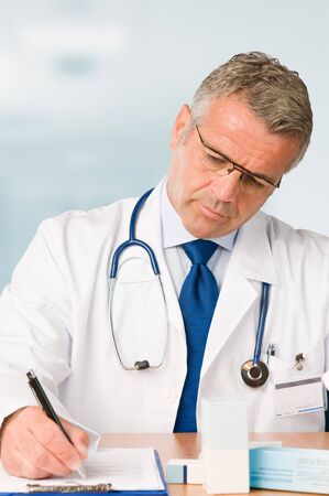 Mature doctor writing and prescribe a medical exam in his modern clinic office *Please note: the Doctor Label is made by myself with a personal design* Stock Photo - 7889589
