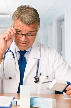 Mature satisfied doctor examining a medication's case to make prescriptions in his clinic office *Please note: the Doctor Label is made by myself with a personal design* Stock Photo - 7889591