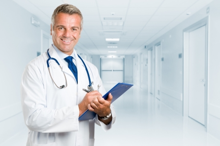 Happy smiling mature doctor writing on clipboard in a modern hospital photo
